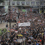 Decenas de miles de persones con camisetas negras, y llevando pancartas, llenan una calle comercial en Hong Kong; forman partede una manifestación masiva contra la extradición, 16 de junio de 2019 (AP Photo/Vincent Yu)